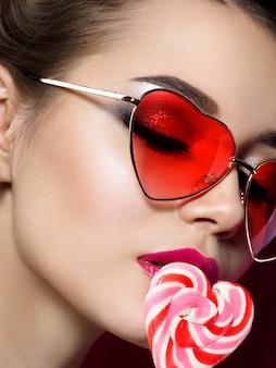 Nahaufnahmeporträt der jungen schönen frau rot, die herzförmige sonnenbrille isst, die lollypop isst. rauchige augen und rote lippen im frühling oder sommer bilden. valentinstag, liebe oder make-up-konzept.