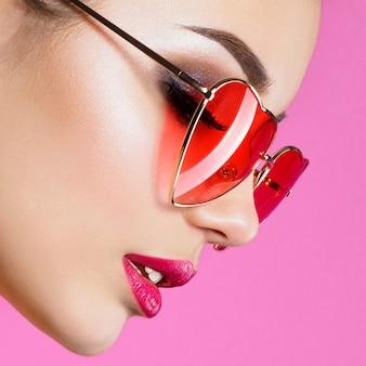Nahaufnahmeporträt der jungen schönen frau rot, die herzförmige sonnenbrille trägt. rauchige augen und rote lippen
