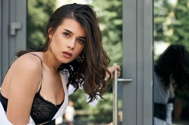 Nahaufnahmeporträt der kaukasischen frau des brunette mit dem perfekten make-up, das draußen den türknauf hält. seitenansicht des jungen weiblichen modells, das tragenden spitzen-bh und weißes hemd aufwirft.