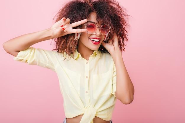 Nahaufnahmeporträt der kühlen frau mit bronzehaut, die niedliche gelbe kleidung und rosa sonnenbrille trägt. aktives weibliches mulattenmodell, das hände tanzt und winkt.