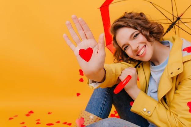 Nahaufnahmeporträt der lachenden dame, die regenschirm und papier rotes herz hält. studioaufnahme des brünetten blassen mädchens, das während des fotoshootings am valentinstag lächelt.