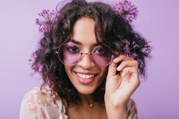 Nahaufnahmeporträt der lächelnden braunäugigen frau mit blumen im schwarzen haar. afrikanische glückselige dame in der sonnenbrille, die aufwirft.