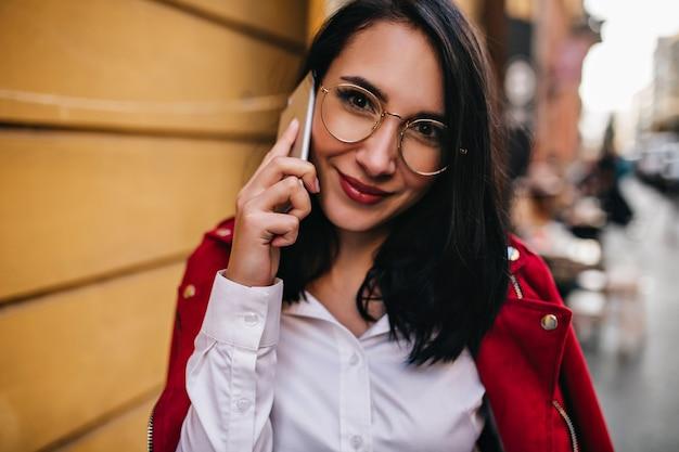 Nahaufnahmeporträt der lächelnden brünetten frau mit den roten lippen, die am telefon sprechen