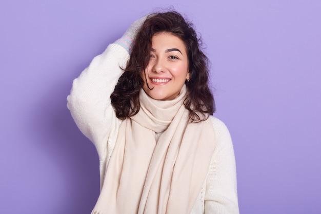 Nahaufnahmeporträt der lächelnden entzückenden frau, die schwarzes lockiges haar hat