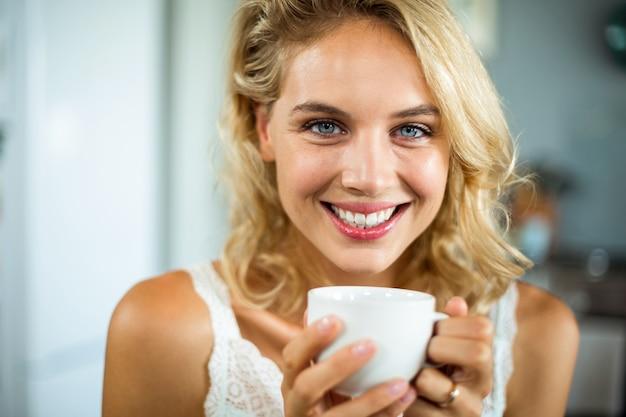 Nahaufnahmeporträt der lächelnden jungen frau, die kaffee trinkt