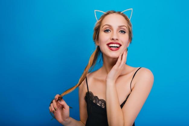 Nahaufnahmeporträt der lächelnden jungen hübschen frauen, die sich auf der party amüsieren und posieren. schwarzes kleid und stirnband mit katzenohren tragen.