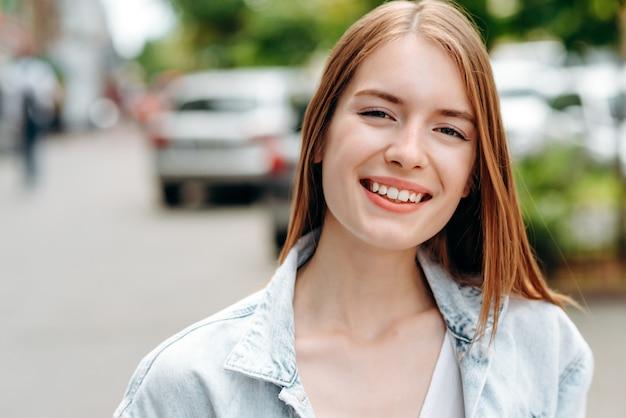 Nahaufnahmeporträt der lächelnden rothaarfrau, die im freien steht