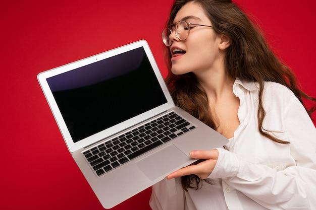 Nahaufnahmeporträt der lustigen schönen lächelnden glücklichen jungen frau, die computerlaptop anschaut hält