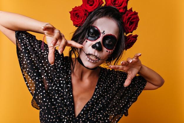 Nahaufnahmeporträt der mexikanischen hexe mit gemaltem gesicht. frau, die im orange studio aufwirft.