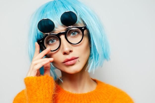 Nahaufnahmeporträt der modefrau mit großen blauen augen. junge frau, die cyan perücke, sonnenbrille und orange pullover trägt.