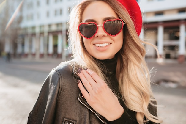 Nahaufnahmeporträt der modischen blonden frau im roten hut und in der stilvollen sonnenbrille, die in der straße gehen. mode frühling sommer foto der entzückenden frau
