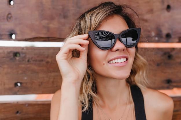 Nahaufnahmeporträt der nachdenklichen gebräunten frau, die ihre schwarze sonnenbrille berührt. schönes kurzhaariges mädchen lokalisiert auf holzwand.
