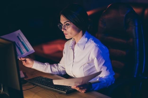 Nahaufnahmeporträt der netten attraktiven stilvollen qualifizierten fokussierten fokussierten dame-ökonomen-geschäftsführerin-vermarkter, die einkommensgewinn-investitionsrate-ausgabenfortschrittsfrist bei nachtdunkelarbeitsplatzstation analysiert
