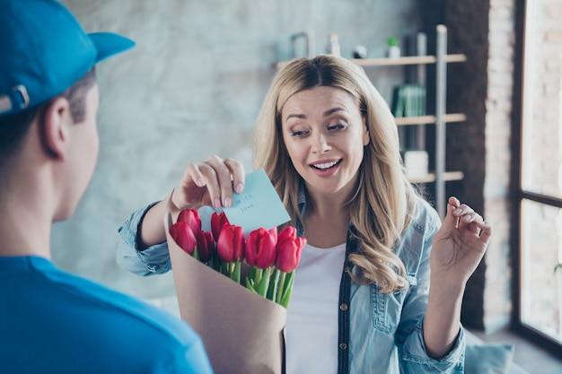 Nahaufnahmeporträt der netten welligen frau, die glückwunschkarte rote blumen erhält