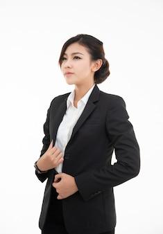Nahaufnahmeporträt der niedlichen glücklichen asiatischen frau im schwarzen anzug, der lokalisiert auf weißem studio sucht