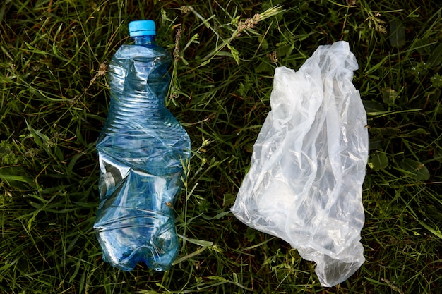 Nahaufnahmeporträt der plastiktüte und der gebrauchten plastikflasche, müll in der wiese, müll im feld, ökologische probleme, abfall, umweltverschmutzung, benutzte plastiksachen.