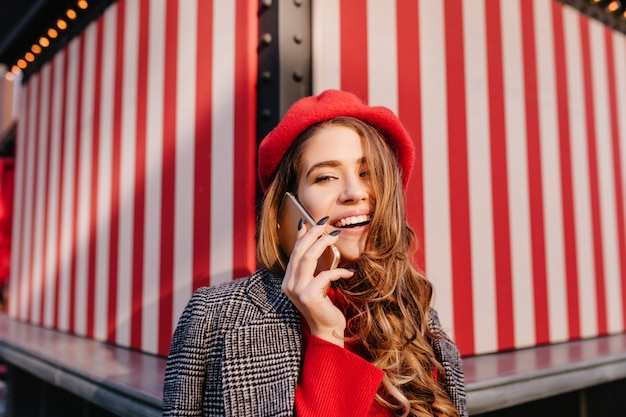 Nahaufnahmeporträt der prächtigen frau mit glänzendem haar, das am telefon auf gestreiftem hintergrund spricht