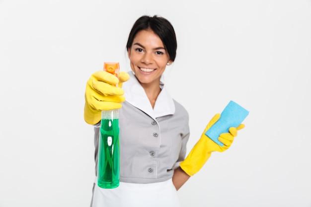 Nahaufnahmeporträt der professionellen haushälterin in uniform und gelben gummihandschuhen, die den reiniger auf sie sprühen
