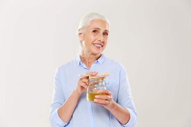 Nahaufnahmeporträt der reizenden reifen frau, die honigglas mit löffel hält