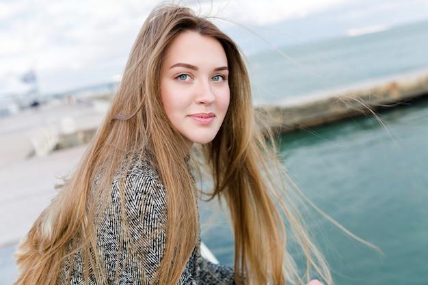 Nahaufnahmeporträt der reizenden reizenden frau mit glücklichem lächeln geht nahe dem meer