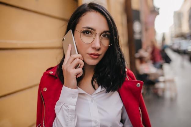 Nahaufnahmeporträt der reizenden schwarzhaarigen frau in der roten jacke, die mit smartphone auf stadtmauer aufwirft