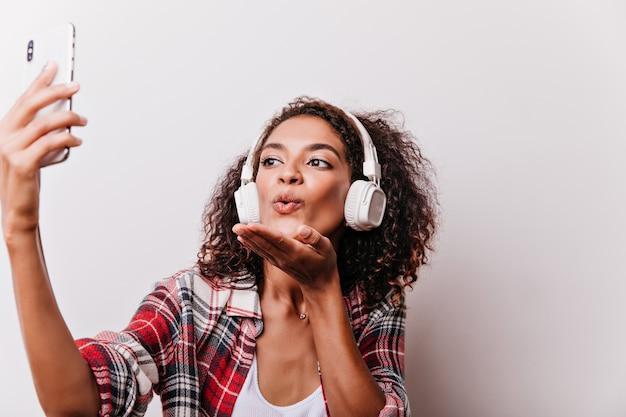 Nahaufnahmeporträt der romantischen schwarzen frau, die luftküsse sendet, während musik hört. modische junge dame in kopfhörern mit smartphone für selfie.