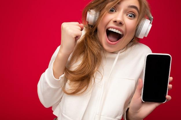 Nahaufnahmeporträt der schockierten emotionalen attraktiven jungen blonden frau, die weißen hoodie lokalisiert trägt