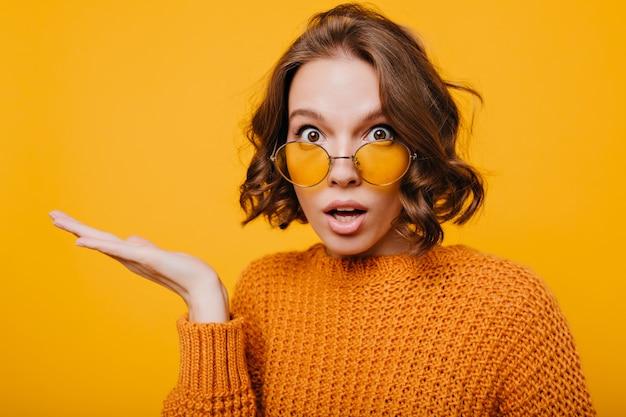 Nahaufnahmeporträt der schockierten jungen dame mit großen braunen augen und offenem mund