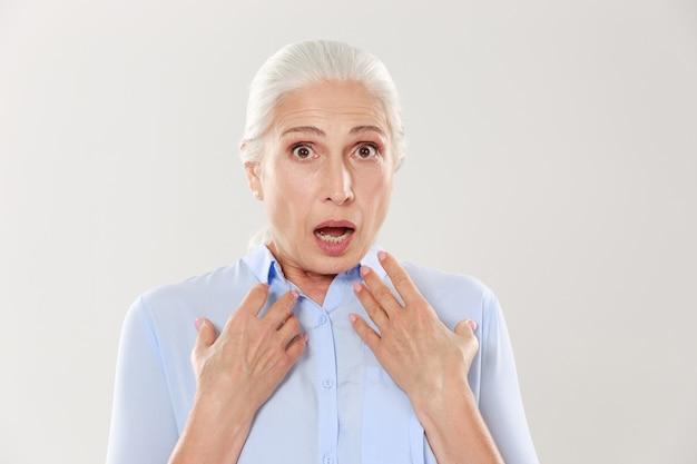 Nahaufnahmeporträt der schockierten reifen frau im blauen hemd