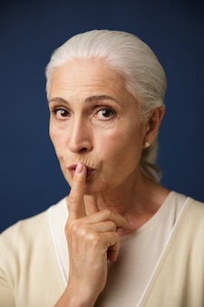 Nahaufnahmeporträt der schönen alten frau, die stille geste zeigt