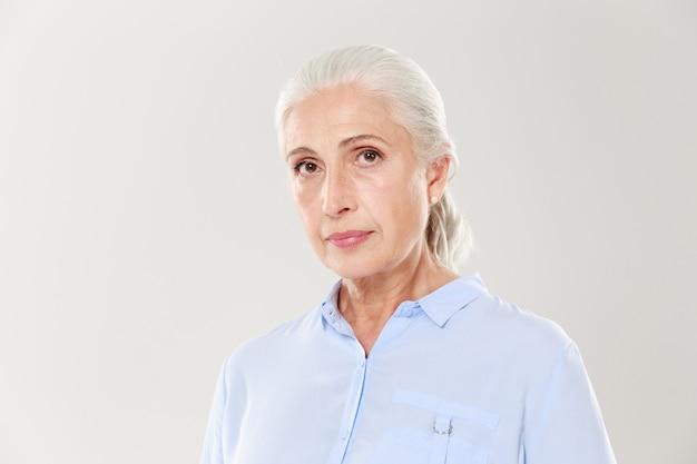 Nahaufnahmeporträt der schönen alten frau im blauen hemd