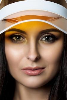 Nahaufnahmeporträt der schönen erwachsenen frau, die gelbes visier trägt.