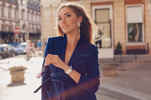 Nahaufnahmeporträt der schönen frau gekleidet in der stilvollen blauen jacke, die in der sonnigen straße des herbstes geht