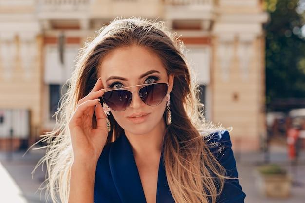 Nahaufnahmeporträt der schönen frau gekleidet in der stilvollen blauen jacke, die in der sonnigen straße des herbstes trägt elegante sonnenbrille geht