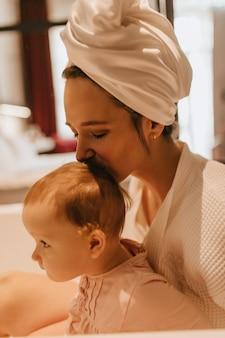 Nahaufnahmeporträt der schönen frau im handtuch auf dem kopf, der ihr baby in der krone küsst.