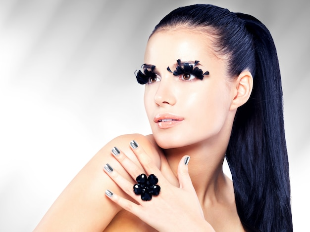 Nahaufnahmeporträt der schönen frau mit langem schwarzen falschen wimpernmake-up und goldenen nägeln