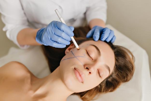 Nahaufnahmeporträt der schönen frau während der vorbereitung zur kosmetiktherapie im schönheitssalon. professionelle dermatologische eingriffe, heben, verjüngen
