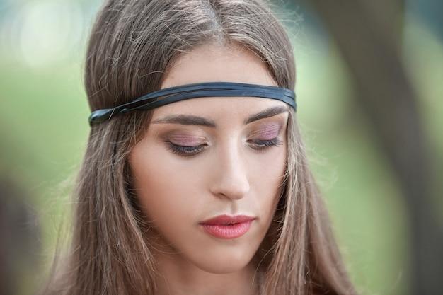 Nahaufnahmeporträt der schönen hippiefrau auf unscharfem laubhintergrund
