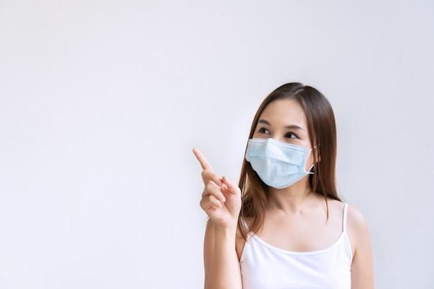Nahaufnahmeporträt der schönen jungen asiatischen frau mit schützender gesichtsmaske, die mit zeigefinger nach oben zeigt, lokalisiert auf weißer wand. positives denkkonzept. speicherplatz kopieren