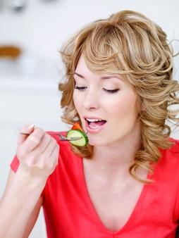 Nahaufnahmeporträt der schönen jungen essenden frau - drinnen