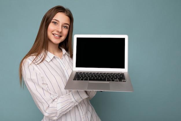 Nahaufnahmeporträt der schönen jungen frau, die einen netbook-computer an der kamera hält