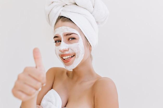 Nahaufnahmeporträt der schönen jungen frau, die mit handtüchern nach dem bad lächelt, machen kosmetische maske auf ihrem gesicht.
