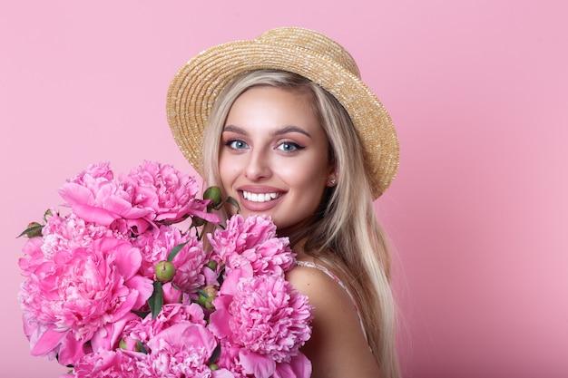 Nahaufnahmeporträt der schönen jungen frau im strohhut, der pfingstrosenblumenstrauß über rosa hält