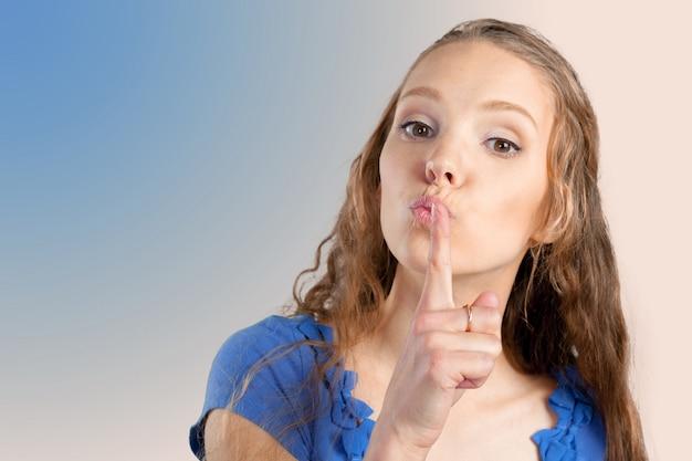 Nahaufnahmeporträt der schönen jungen frau mit dem finger auf lippen
