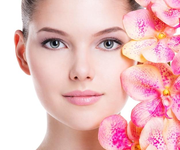 Nahaufnahmeporträt der schönen jungen frau mit gesunder haut und rosa blumen nahe gesicht - lokalisiert auf weiß.