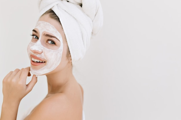 Nahaufnahmeporträt der schönen jungen frau mit handtüchern nach dem bad machen kosmetische maske auf ihrem gesicht.