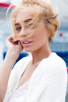 Nahaufnahmeporträt der schönen kaukasischen blonden frau, die draußen geht. schöne frau im weißen hemd. modeporträt der herrlichen frau. junge frau, die spaß in der stadt hat. straßenmode.