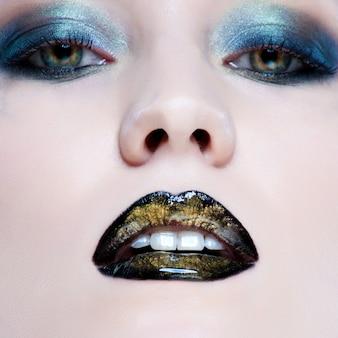 Nahaufnahmeporträt der schönen kaukasischen jungen frau mit perlenzaubermake-up und den schwarzen lippen