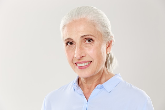 Nahaufnahmeporträt der schönen lächelnden alten frau im blauen hemd