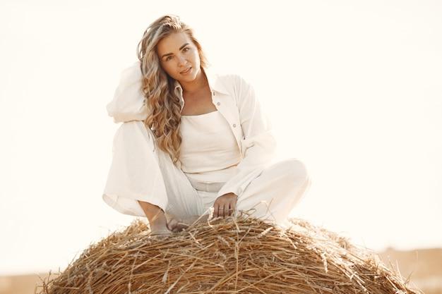 Nahaufnahmeporträt der schönen lächelnden frau. die blondine auf einem heuballen. ein weizenfeld auf dem hintergrund.